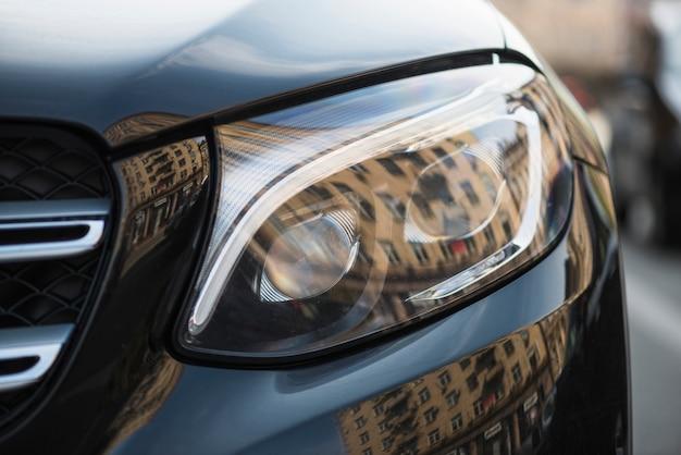 Stijlvolle koplamp van donkere auto op straat