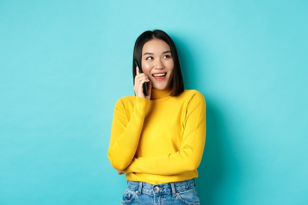 Stijlvolle koreaanse vrouw die telefoon belt, op smartphone praat en gelukkig kijkt in de rechterbovenhoek, zorgeloos lacht, in ontspannen pose over blauwe achtergrond staat