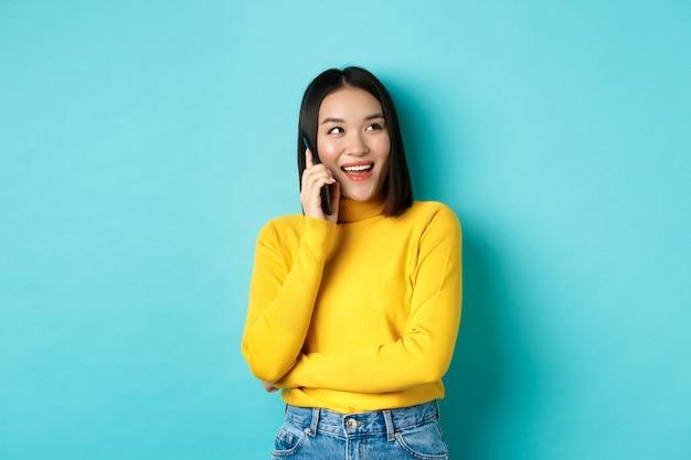 Stijlvolle koreaanse vrouw die telefoon belt, op smartphone praat en gelukkig kijkt in de rechterbovenhoek, zorgeloos lacht, in ontspannen pose over blauwe achtergrond staat.