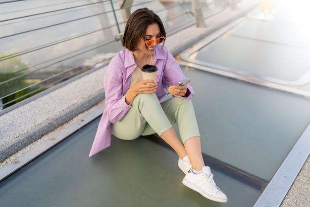 Stijlvolle kortharige vrouw zittend op de moderne brug, genieten van koffie en het gebruik van mobiele telefoon