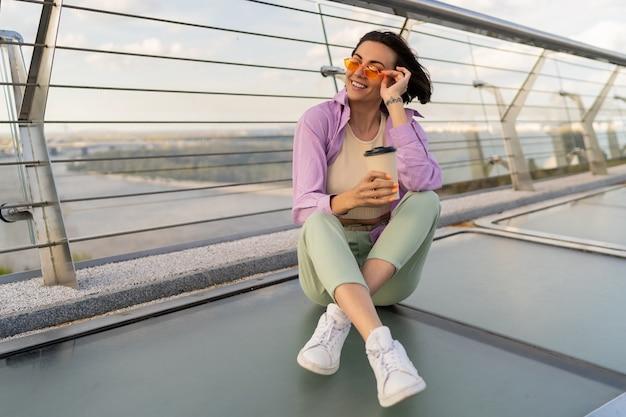 Stijlvolle kortharige vrouw zittend op moderne brug, genieten van koffie