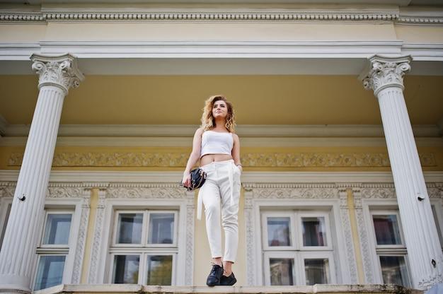 Stijlvolle krullende blonde model meisjesslijtage bij het witte stellen tegen oud uitstekend huis.