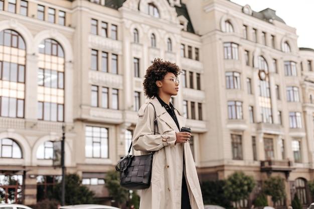 Stijlvolle krullende dame in beige trenchcoat, bril en met zwarte tas houdt koffiekopje vast en loopt in de stad