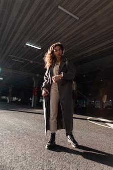 Stijlvolle krullende vrouw in een lange vintage jas met laarzen en een tas loopt op straat bij de parkeerplaats