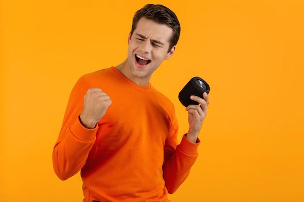 Stijlvolle lachende jonge man in oranje trui met draadloze luidspreker gelukkig luisteren naar muziek plezier op oranje
