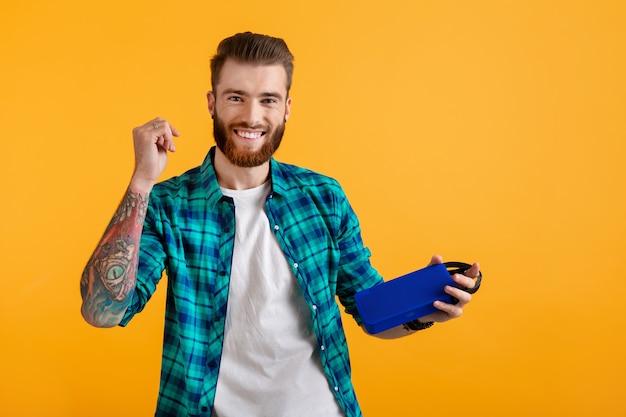 Stijlvolle lachende jonge man met draadloze luidspreker luisteren naar muziek op oranje