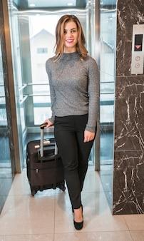 Stijlvolle lachende jonge vrouw komt uit de lift met haar koffer