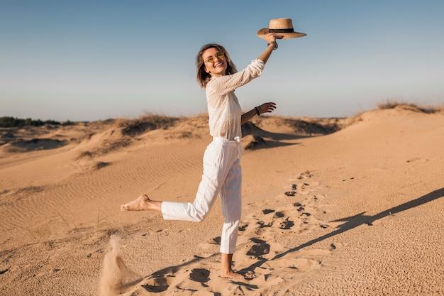 Stijlvolle lachende mooie gelukkige vrouw rennen en springen in woestijnzand in witte outfit met strooien hoed op zonsondergang