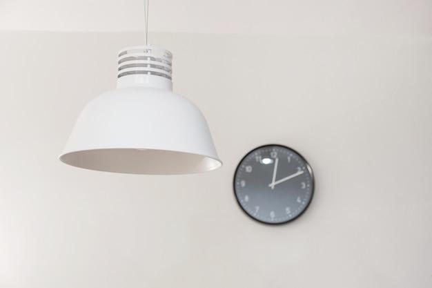 Stijlvolle lamp en klok aan de muur.