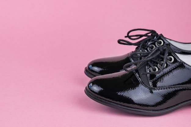 Stijlvolle leren damesschoenen op een felroze achtergrond. modieuze schoolschoenen.