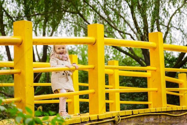 Stijlvolle llittle meisje op een gele brug in het park