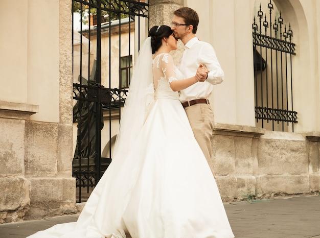 Stijlvolle luxe bruid en elegante bruidegom, knuffelen met tederheid, op de achtergrond van de oude stad lviv