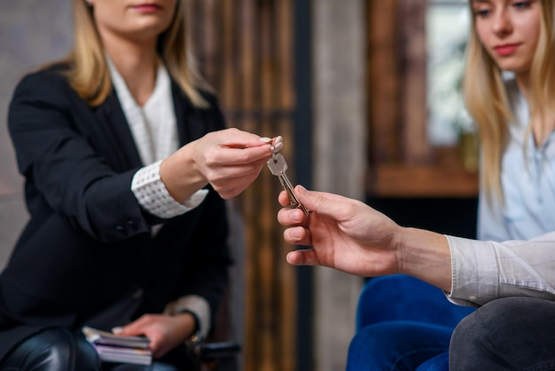 Stijlvolle makelaar met geld aan de kant geven sleutel van flat, huis aan het jonge paar.