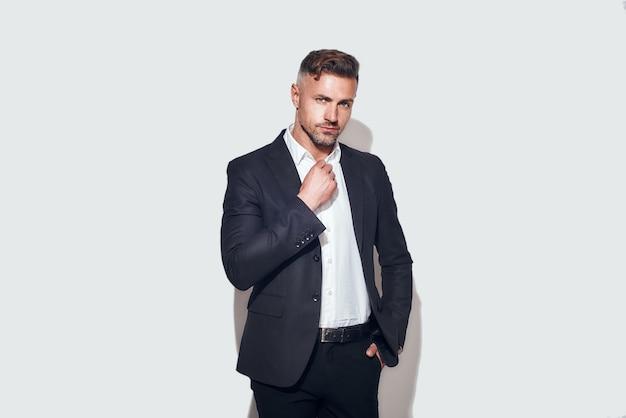 Stijlvolle man, bebaarde zakenman in klassiek pak die hemd aanpast en naar de camera kijkt terwijl hij staat?