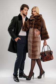 Stijlvolle man en glamour vrouw in bontjas poseren met winter outfit.