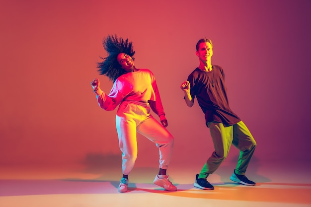 Stijlvolle man en vrouw hiphop dansen in lichte kleding op groene achtergrond in de danszaal in neonlicht. jeugdcultuur, hiphop, beweging, stijl en mode, actie. modieus portret.