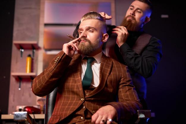 Stijlvolle man geniet van kapsel bij de kapper, hij rookt tijdens het knippen