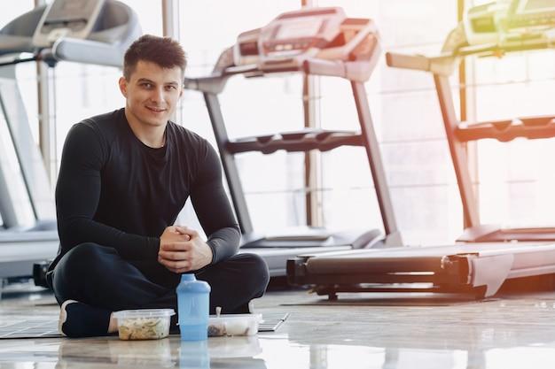Stijlvolle man in de sportschool ontspannen op de vloer en gezond eten.