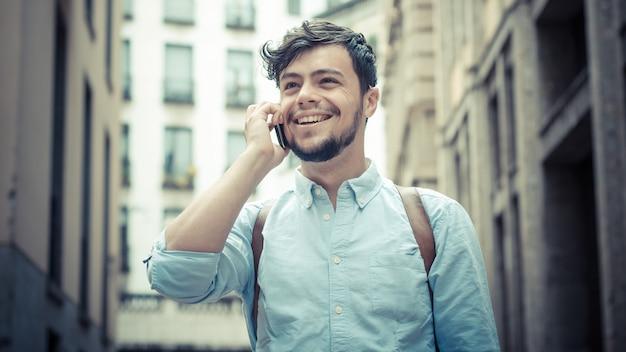 Stijlvolle man in de straat aan de telefoon