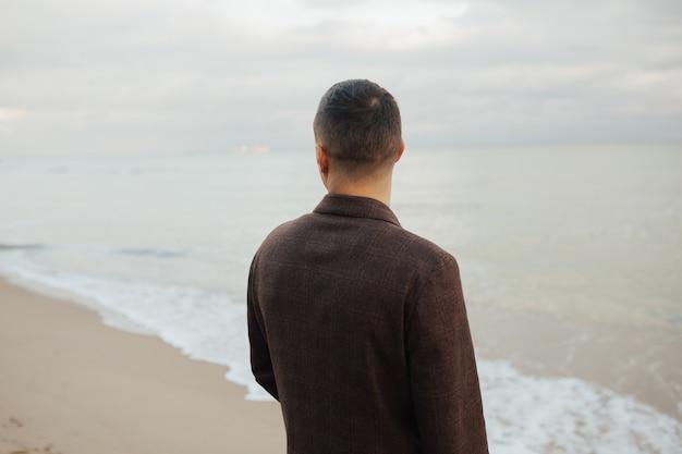 Stijlvolle man in de vacht die het prachtige uitzicht bewondert. hij bewondert het uitzicht op een prachtig zeegezicht.