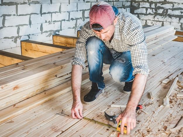 Stijlvolle man in een baseballpet, spijkerbroek en een shirt, werkt met gereedschap op hout in het huis in aanbouw. concept van constructie en reparatie
