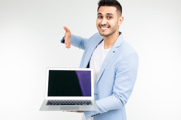 Stijlvolle man in een blauwe jas toont een laptop scherm met een lege sjabloon voor het invoegen van een site op een witte studio achtergrond