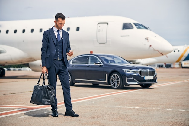 Stijlvolle man in een pak die naar zijn telefoon kijkt terwijl hij voor een auto in de buurt van een vliegtuig staat