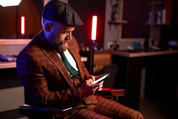 Stijlvolle man in formeel kostuum en hoed smartphone kijken