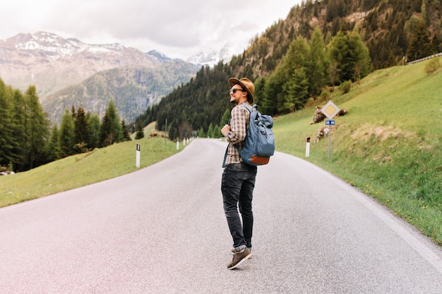 Stijlvolle man in goed humeur buiten wandelen met rugzak en kijkt rond met een glimlach, genietend van het weekend in italië