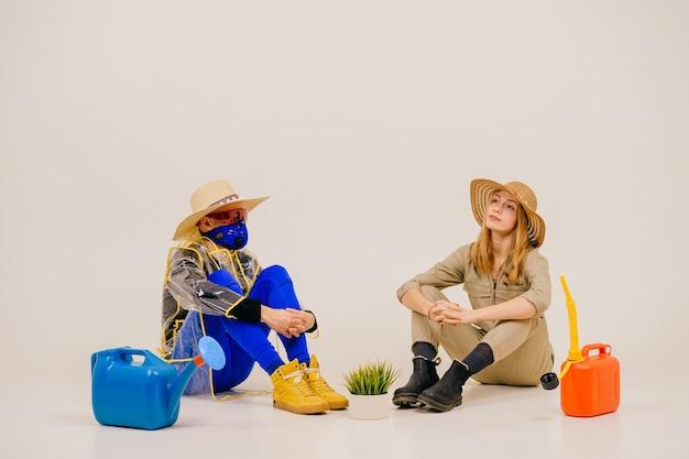 Stijlvolle man in het masker en vrouw in strooien hoeden poseren met gieter over witte muur