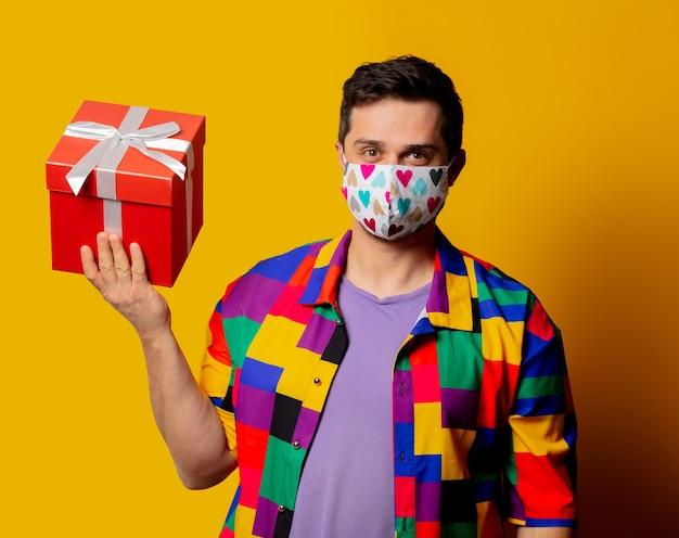 Stijlvolle man in jaren 90-shirt en gezichtsmasker met geschenkdoos