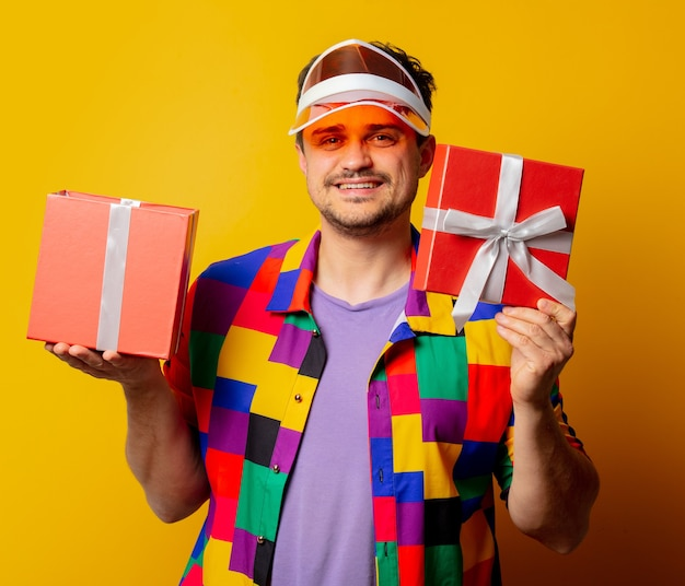 Stijlvolle man in jaren 90 shirt en hoed met geschenkdoos