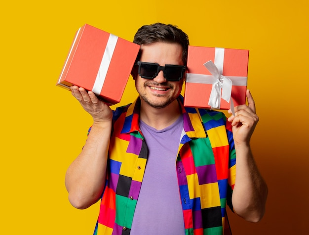 Stijlvolle man in jaren 90-shirt met geschenkdoos