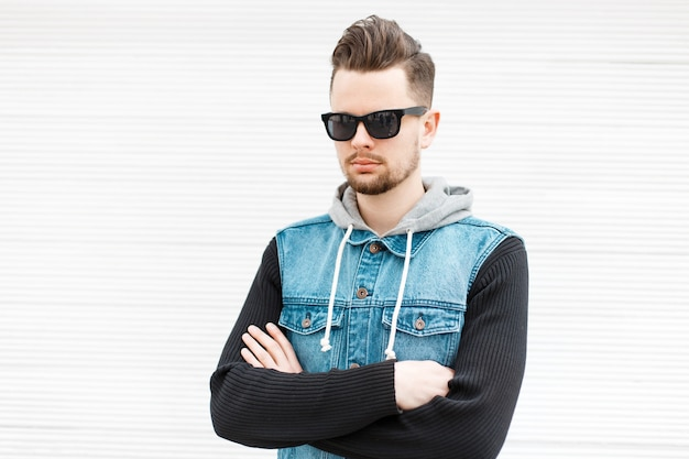 Stijlvolle man in jeans kleding met zonnebril poseren in de buurt van witte houten muur