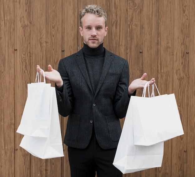 Stijlvolle man met boodschappentassen in beide handen