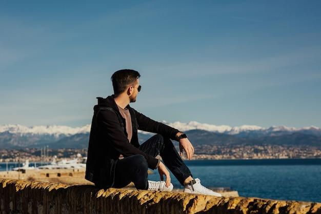 Stijlvolle man met bril genietend van het uitzicht op de zee en de sneeuwende berg.