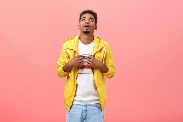 Stijlvolle man met een donkere huid die lijdt aan warm weer en uitademt en zwaait met een t-shirt om af te koelen terwijl hij zich ongemakkelijk voelt over een roze achtergrond die ongepaste kleding draagt voor een zonnige zomerdag. ruimte kopiëren