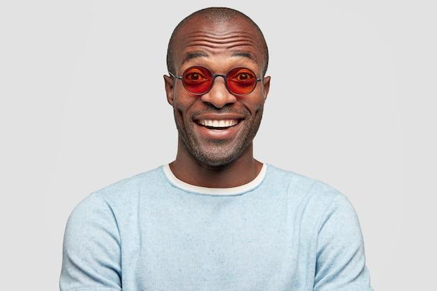 Stijlvolle man met een positieve glimlach, draagt modieuze rode tinten, in een hoge geest zoals grappige anekdote van gesprekspartner hoort