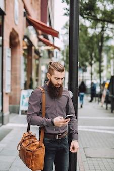 Stijlvolle man met lange baard met telefoon