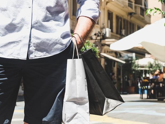 Stijlvolle man met twee tassen op straat in de zomer, zonnige dag. concept van stijl, mode en schoonheid