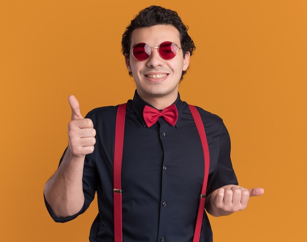Stijlvolle man met vlinderdas die een bril en bretels draagt die aan de voorkant glimlachen, blij en positief, duimen opdagen die over oranje muur staan