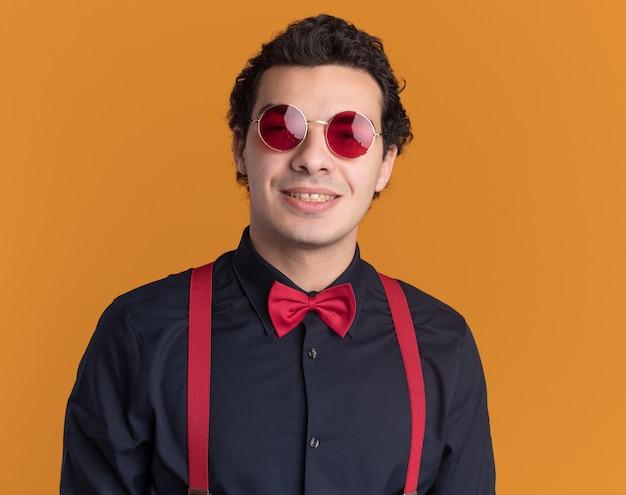 Stijlvolle man met vlinderdas die een bril en bretels draagt die aan de voorkant glimlachend blij en positief staan kijken over oranje muur