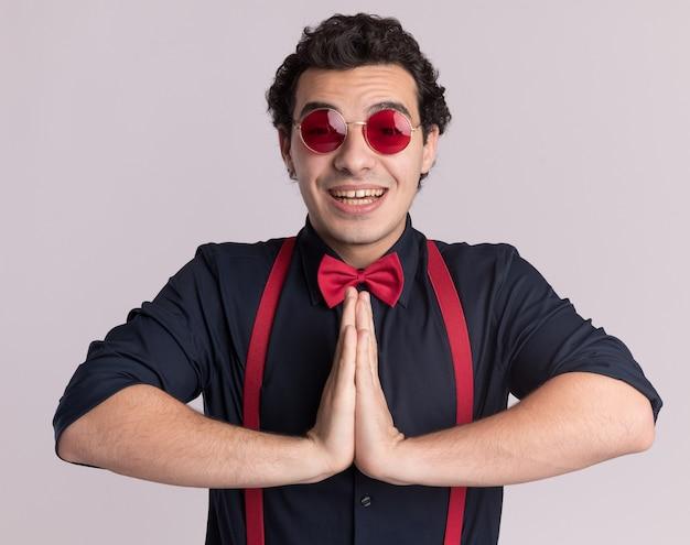 Stijlvolle man met vlinderdas die een bril en bretels draagt die handpalmen bij elkaar houden als namaste-gebaar, blij en vrolijk glimlachend staande over witte muur