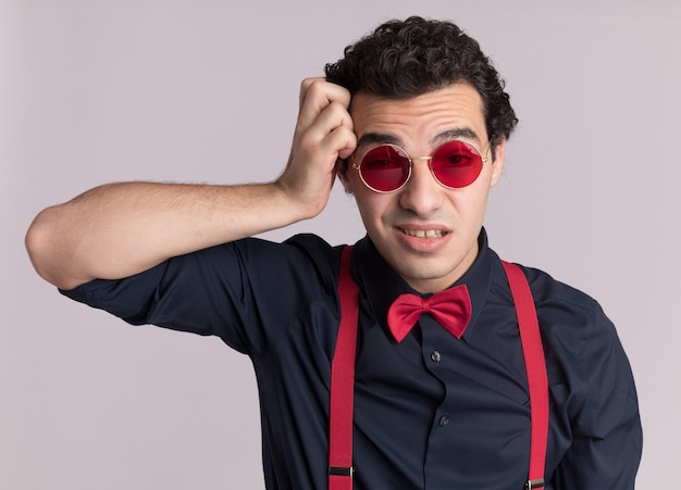 Stijlvolle man met vlinderdas die een bril en bretels draagt die naar de voorkant kijkt, verward en erg angstig over een witte muur staat