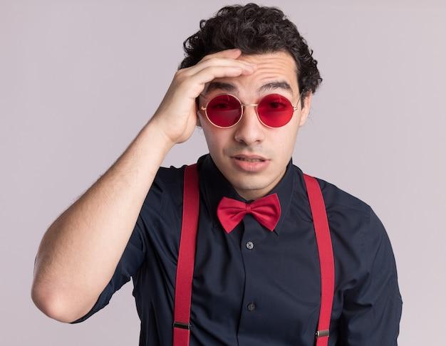 Stijlvolle man met vlinderdas die een bril en bretels draagt die naar de voorkant kijkt, verward met de hand op zijn voorhoofd, staande over de witte muur