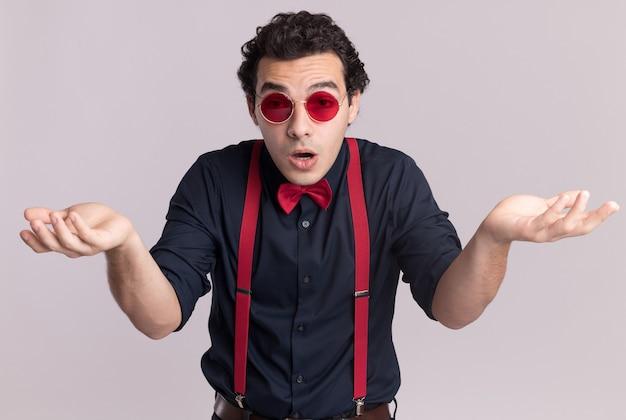 Stijlvolle man met vlinderdas die een bril en bretels draagt die naar de voorkant kijkt, verward schouderophalend, zonder antwoord staande over een witte muur