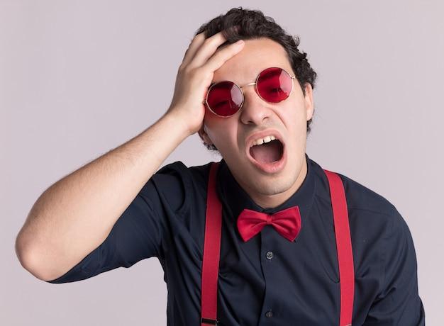 Stijlvolle man met vlinderdas die een bril en bretels draagt en naar de voorkant kijkt, verward met de hand op zijn hoofd, schreeuwend met geïrriteerde uitdrukking staande over de witte muur