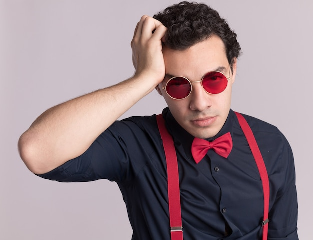 Stijlvolle man met vlinderdas die een bril en bretels draagt en naar de voorkant kijkt, verward met de hand op zijn hoofd voor een fout die over de witte muur staat