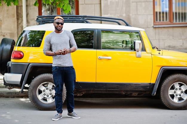 Stijlvolle man op grijze trui en zwarte zonnebril gesteld op straat tegen gele auto