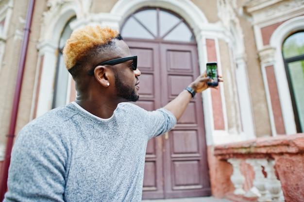 Stijlvolle man op grijze trui en zwarte zonnebril poseerde op straat modieuze zwarte man selfie maken op telefoon.